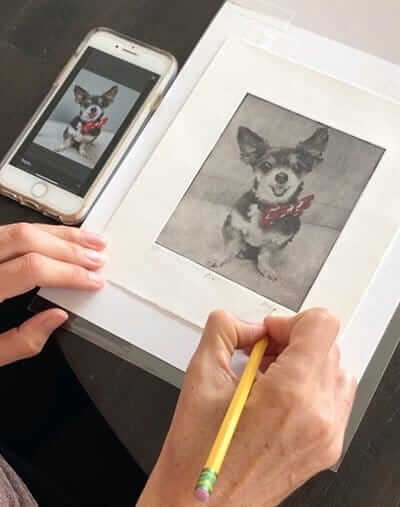 artist hands signing pet portrait sympathy gift of chihuahua next to phone photo of chihuahua