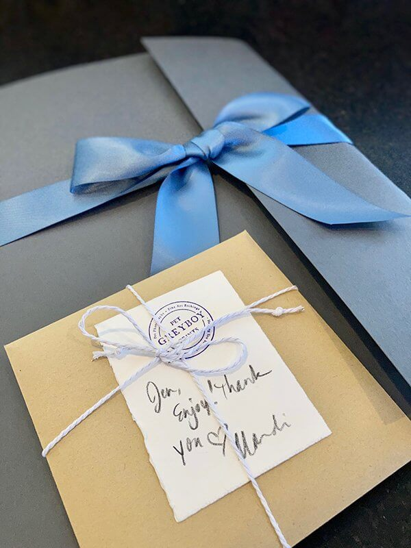Dog Portrait Gift Wrapped in Gray Folder and Blue Ribbon with Handwritten Note